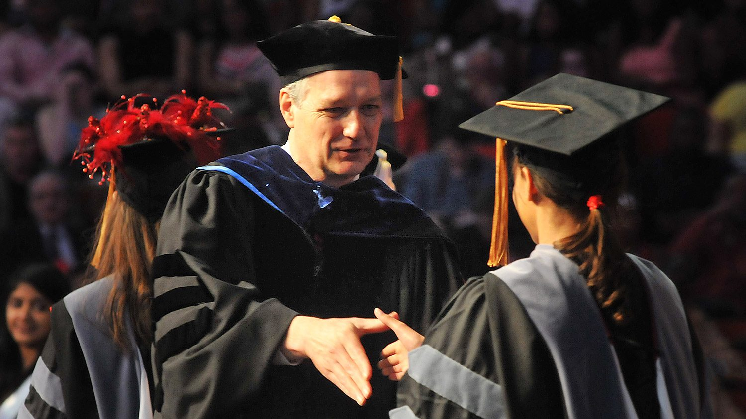 Executive Vice Chancellor and Provost Warwick Arden shakes a students' hand at commencement