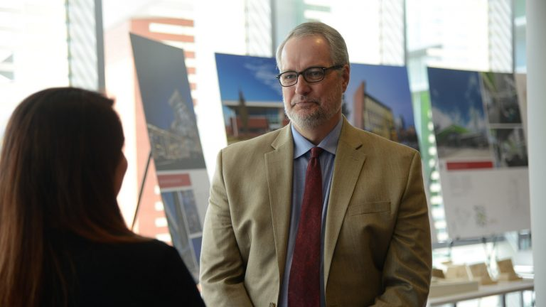Provost talking to staff member