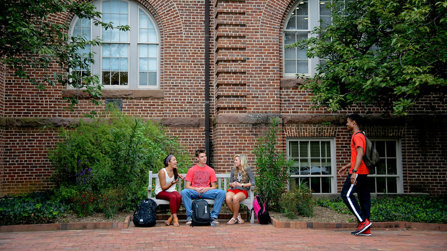 Students chat in front of Holladay Hall on campus.
