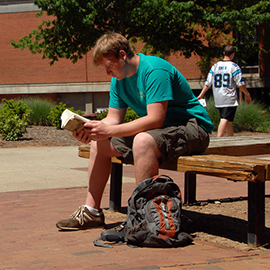 Student reads between classes on a sunny Spring day on main campus.