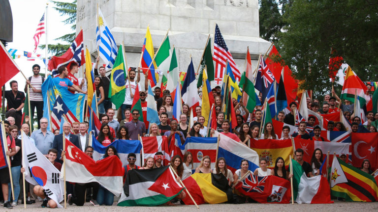 International students with flags at the Memorial Belltower