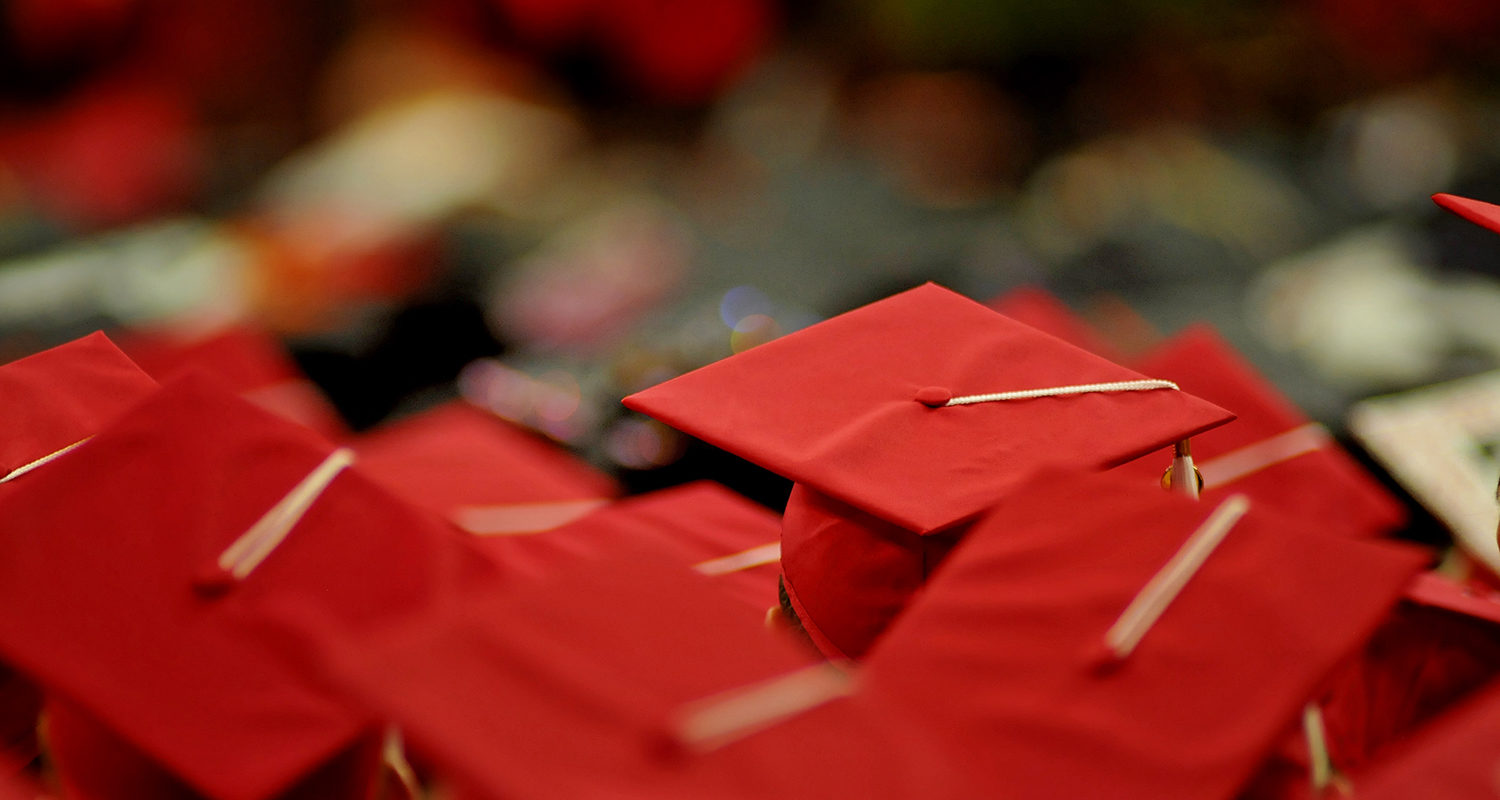 Red mortarboards viewed from above during graduation ceremony.