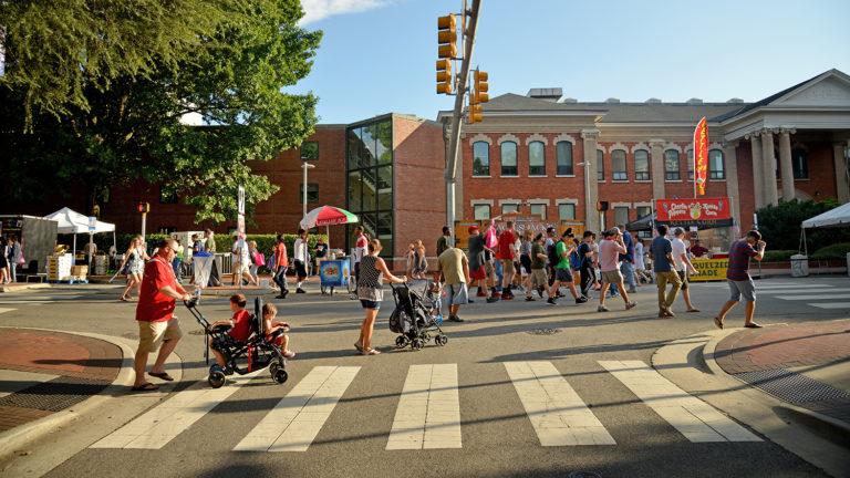 Family walks up Hillsborough Street during Packapalooza.