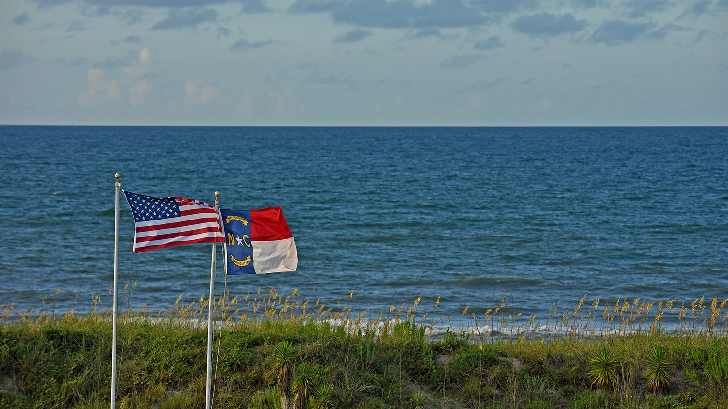 US and NC flags flap in the summer breeze along the dunes of Atlantic Beach.