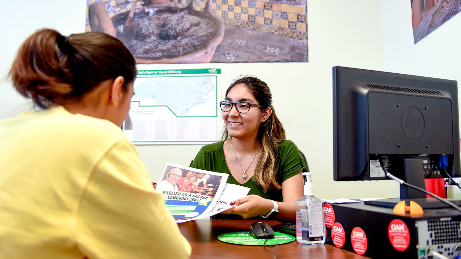 Female NC State student providing information to another female at a desk